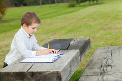 Boy drawing. With a yellow pencil on a paper sitting at a wooden table in the park Stock Photo