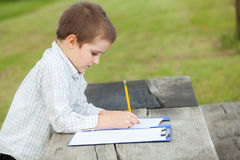 Boy drawing. With a yellow pencil on a paper sitting at a wooden table in the park Royalty Free Stock Photos