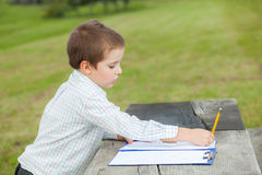 Boy drawing. With a yellow pencil on a paper sitting at a wooden table in the park Stock Photography