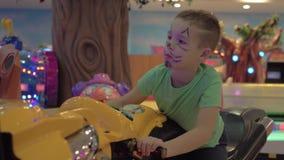 Child having fun with motorbike racing game. Boy with drawn cat face playing motorbike racing simulator in indoor amusement park stock video footage