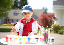 The boy draws. Paints outside Stock Photography
