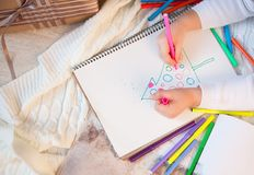The boy draws in the album markers a Christmas green tree. A child draws christmas, a Christmas tree, snow, lying under a Christmas tree with pencils. Holiday Royalty Free Stock Image