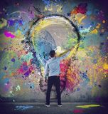 Boy draws with a brush a big light bulb. Concept of innovation and creativity. Boy draws with a brush an abstract big light bulb. Concept of innovation and royalty free stock photo