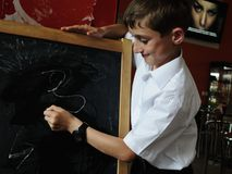 The boy draws a chalk on a blackboard Royalty Free Stock Image