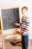 Boy draws a chalk on a board Stock Images