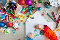 The child draws a Christmas tree with markers and colored pencil. A boy draws a Christmas tree. Child`s drawing Christmas. The child lies on the floor and draws Royalty Free Stock Photos