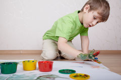 Boy draws color paints with his fingers Royalty Free Stock Images