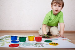Boy draws color paints and makes handprints Stock Photo