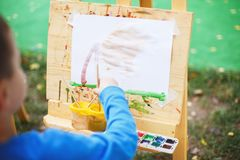 Boy draws on the easel. royalty free stock photo