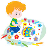 Boy draws an Easter egg. Little boy drawing a colorfully decorated Easter egg Royalty Free Stock Photography