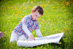 Boy draws on the grass in field Royalty Free Stock Photography