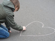 Boy draws heart with chalk on the ground Royalty Free Stock Photo