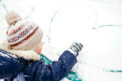The boy draws heart on snow. Outdoor. Winter, love, friendship, concept. Royalty Free Stock Photos