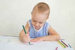 Boy draws. Little boy at a desk learning to draw with markers and pencils. Child with a felt-tip pen in hand. Photo with limited depth of field Stock Photography