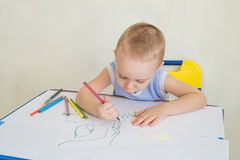 Boy draws. Little boy at a desk learning to draws with pencils. Child with a pencil in hand. Photo with copy space and limited depth of field Royalty Free Stock Photography