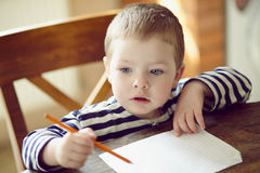 Boy draws. Boy draws a pencil on a sheet of paper Stock Images