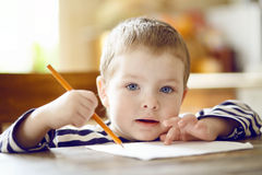 Boy draws. Boy draws a pencil on a sheet of paper Royalty Free Stock Images