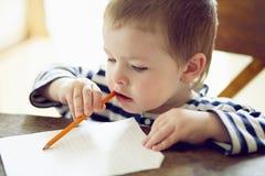 Boy draws. Boy draws a pencil on a sheet of paper Stock Photography