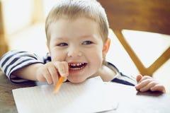 Boy draws. Boy draws a pencil on a sheet of paper Stock Photos