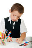 The boy draws pencils in an album on a white background Royalty Free Stock Image
