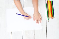 A boy draws with pencils on a white sheet of paper. Developing c. A boy draws with pencils on a white sheet of paper Stock Photos