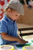 Boy draws with plasticine Stock Photography