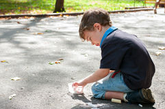 Boy draws on the road with chalk. Three four year old boy squatted on the sidewalk and draw with chalk Stock Image