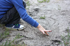 The boy draws in the sand. Stock Images