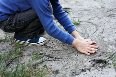The boy draws in the sand. Royalty Free Stock Photos