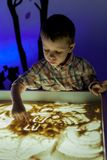 The boy draws sand in the sand stock photo