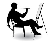 Boy draws. Boy sitting at his easel and paints on canvas Stock Image