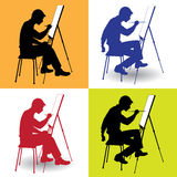 Boy draws. Boy sitting at his easel and paints on canvas Royalty Free Stock Photography