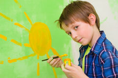 Boy draws the sun. Cute boy draws the sun on the wall at home Royalty Free Stock Image