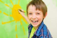 Boy draws the sun. Cute boy draws the sun on the wall at home Stock Photography
