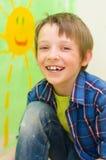 Boy draws the sun. Happy boy draws the sun on the wall Stock Image