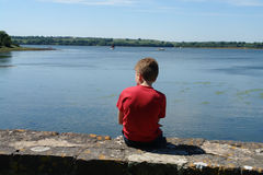 Boy Dreaming. A young boy sitting on a wall in Wales watching the boats on the tidal river Stock Photos