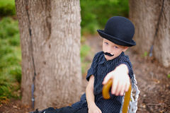 Boy dressed as Charlie Chaplin. Young boy in countryside with bowler hat, moustache and walking stick dressed as Charlie Chaplin Royalty Free Stock Photography