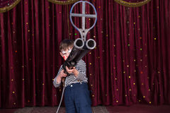 Boy Dressed as Clown Holding Large Gun on Stage Stock Photography