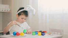 A boy dressed as a hare paints an Easter egg.Easter. Holiday. White egg. A boy dressed as a hare paints eggs green.Easter. Holiday. Rabbit costume stock footage