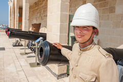 Boy dressed as in old English military uniform in front of the cannons in Valletta, Malta Stock Photos