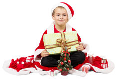 Boy dressed as Santa and holding present sitting Stock Images