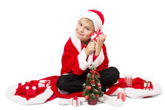 Boy dressed as Santa opens Christmas gifts on a white Royalty Free Stock Photo