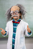 Boy dressed as scientist gesturing thumbs up sign. Portrait of boy dressed as scientist gesturing thumbs up sign in classroom Stock Photography