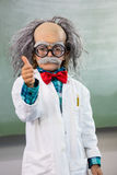 Boy dressed as scientist with thumbs up sign. Boy dressed as scientist gesturing thumbs up sign in classroom Stock Photo