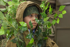 Boy dressed as a scout disguised in foliage. Portrait of a boy dressed as a scout disguised in foliage Stock Photo