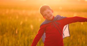 Little boy plays and dreams of a super hero at sunset. A boy dressed as a super hero standing in a mask and a red cloak runs laughing at the sunset in the summer stock video footage
