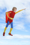 Boy dressed as superhero flying against cloudy sky Royalty Free Stock Photos
