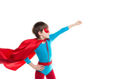 Boy dressed as superhero poses in studio. Royalty Free Stock Image