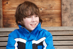 Boy Dressed For Cold Weather. Sitting On Wooden Bench Stock Photos