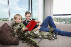 Boy dressed in dinosaur costume reading picture book with father on sofa bed at home Royalty Free Stock Image